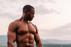 英俊的黑人非裔美国人的运动员画象日出天空背景的 免版税图库摄影