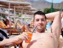 英俊的年轻人饮用的汁液画象在水池的 免版税库存图片