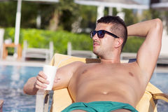 英俊的年轻人饮用的汁液画象在水池的 免版税图库摄影