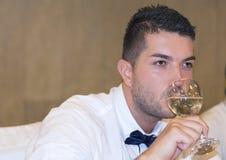 英俊的年轻人饮用的白葡萄酒 免版税库存照片