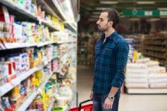 英俊的年轻人购物在杂货超级市场 库存图片