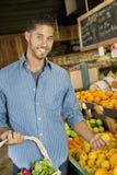 英俊的年轻人购物画象果子的在市场上 免版税图库摄影