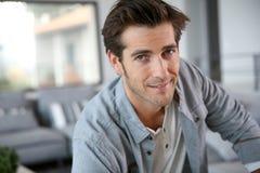 英俊的年轻人画象在客厅 库存图片