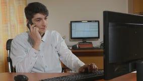 英俊的年轻商人程序员谈话在他的智能手机 股票视频