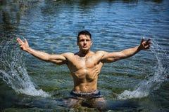 英俊的年轻爱好健美者在海,飞溅水  免版税库存图片