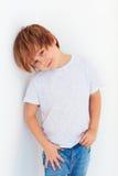 英俊的年轻男孩,摆在白色墙壁附近的孩子 免版税库存图片
