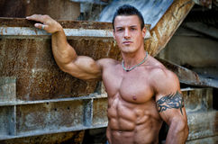 英俊的年轻肌肉人用在生锈的金属结构的手 库存照片