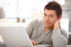 英俊的年轻人纵向有计算机的 免版税图库摄影
