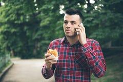 英俊的年轻食人的三明治autdoor 他拿着一个电话 免版税库存照片