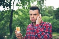 英俊的年轻食人的三明治autdoor 他拿着一个电话 免版税库存图片