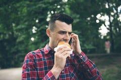 英俊的年轻食人的三明治autdoor 他拿着一个电话 库存照片
