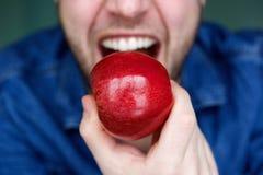 英俊的年轻食人的红色苹果 图库摄影