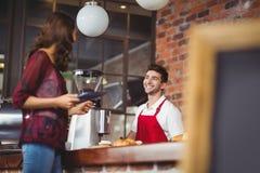 英俊的barista谈论与顾客 免版税图库摄影