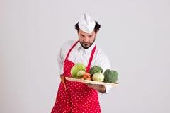 英俊的Headcook拿着有菜的一个柳条盘子 库存图片