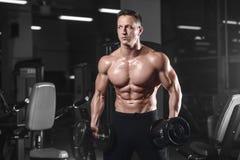 英俊运动健身在健身房的人摆在和火车 免版税库存照片