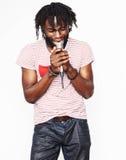 年轻英俊非裔美国人男孩唱歌情感与在白色背景的话筒,在行动打手势 免版税图库摄影