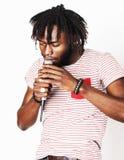 年轻英俊非裔美国人男孩唱歌情感与在白色背景的话筒,在行动打手势 免版税库存图片