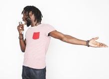 年轻英俊非裔美国人男孩唱歌情感与在白色背景隔绝的话筒,在行动打手势 库存图片
