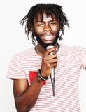 年轻英俊非裔美国人男孩唱歌情感与在白色背景隔绝的话筒,在行动打手势 图库摄影