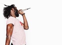 年轻英俊非裔美国人男孩唱歌情感与在白色背景隔绝的话筒,在行动打手势 库存照片