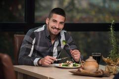 年轻英俊食人在餐馆 免版税库存图片