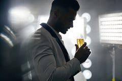 英俊,典雅的人饮用的香槟的画象 库存图片