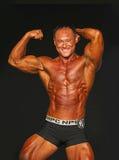 英俊,坚固性爱好健美者显示强有力的体质 免版税库存照片