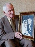 英俊80拿着他的婚礼照片的正岁老人 永远爱概念 免版税库存照片