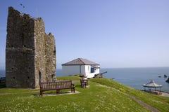 英国、Tenby、城堡小山废墟和海岸警备队房子 春天阳光 免版税库存照片