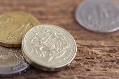 英国一磅,两毛五硬币和欧洲硬币在木 库存图片