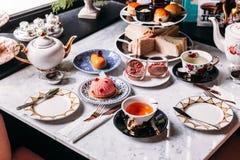 英国下午茶集合包括热的茶、酥皮点心、烤饼、三明治和微型饼在大理石顶面桌上 免版税库存图片