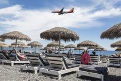 英国便宜的航空公司飞机飞行在海滩在Kamari,圣托里尼 库存照片