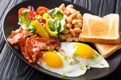 英国健康早餐:两个煎蛋用烟肉,豆, toa 免版税库存照片