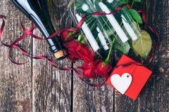 英国兰开斯特家族族徽,两块玻璃,瓶花束酒,有标记的礼物盒在葡萄酒木板 红色上升了 顶视图 免版税图库摄影