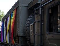 英国军车参加同性恋自豪日游行,装饰用彩虹和LGBT+旗子 免版税库存照片