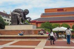 英国图书馆大厦的看法,它的与艾萨克・牛顿雕塑的广场爱德华多・包洛奇和访客 库存照片
