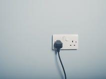 英国壁上插座和绳子在蓝色墙壁上 免版税库存照片