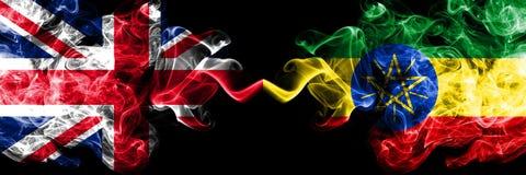 英国对埃塞俄比亚,肩并肩被安置的埃赛俄比亚的发烟性神秘的旗子 英国的厚实的色的柔滑的烟 皇族释放例证