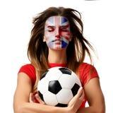 英国爱好者体育红色一致的举行足球的妇女球员庆祝与有风头发的 库存图片