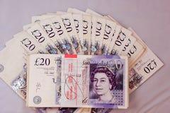 英国磅金钱现金支付薪水赢得货币20pounds收入旅游业大量卷needfull银行收入旅行自由1000 p 免版税库存照片