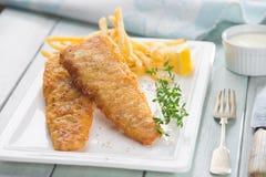 英国筹码鱼快餐桌传统木 油煎的鱼片用炸薯条 图库摄影