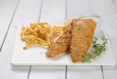 英国筹码鱼快餐桌传统木 油煎的鱼片用炸薯条 免版税图库摄影