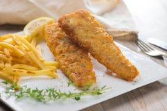 英国筹码鱼快餐桌传统木 油煎的鱼片用炸薯条 免版税库存图片