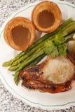 英国膳食用约克夏布丁、绿色芦笋和猪肉ch 图库摄影
