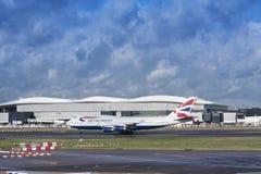 英国航空公司飞行离开在多云d的希思罗机场 库存照片