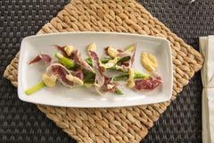 英国芦笋、Iberico火腿&用块菌烹调的蛋黄奶油酸辣酱 库存照片