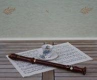 英国茶杯和茶碟有花卉装饰的和银色外缘和一支块长笛在音乐板料  图库摄影