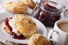 英国酥皮点心:烤饼用果酱和奶茶特写镜头 Ho 免版税库存图片