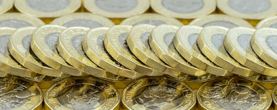 英国金钱新的1英镑硬币被传播的掉下来的堆 库存图片