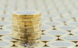英国金钱,在整洁的堆的新的1英镑硬币 免版税库存图片